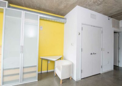 The Hub on Chestnut Apartment interior bedroom with wardobe, closet and yellow accent wall