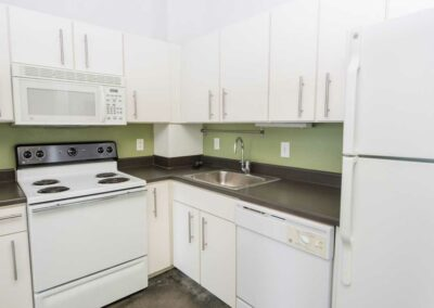 The Hub on Chestnut apartment interior kitchen with white appliances and green accent backsplash